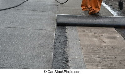 Roofer doing repair waterproofing - Worker underlain rolled...