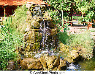 Beautiful waterfall in  garden in summer.