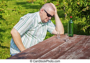Man thinking near bottle of alcohol on table