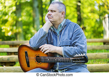 Sad man with guitar in park on benc