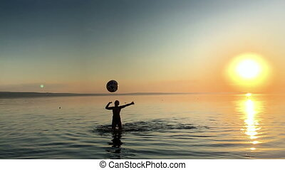 Child playing ball in the water at sunset.