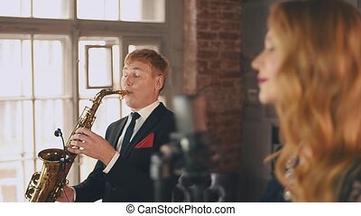 Jazz vocalist perform on stage with saxophonist in dinner...