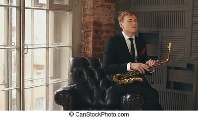 Saxophonist in dinner jacket stand up on stage with golden...