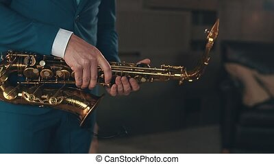 Saxophonist in blue elegant suit play jazz on golden saxophone at stage. Music