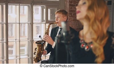 Jazz singer perform on stage with saxophonist. Duet. Live...