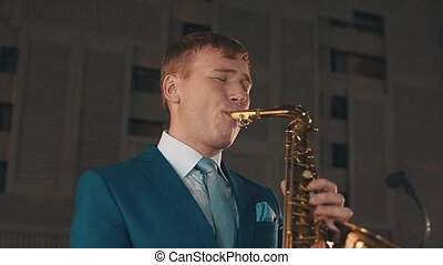 Saxophonist in blue suit play jazz on golden saxophone with microphone. Music.