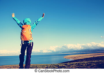 successful woman backpacker hiking on mountain peak