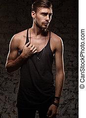 Stylish sexy man stands near a wall