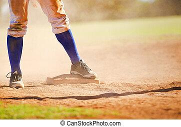 Baseball player on the base - Baseball player wearing blue...