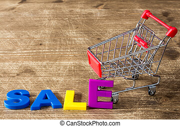 Shopping cart and word SALE - Shopping cart and color...