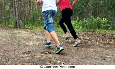 Mother and son running through the woods. Slow motion