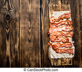 Fried bacon on the fabric. On a wooden table.