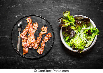 Fried bacon with greens. On black wooden background. - Fried...