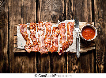 Fried bacon with tomato sauce. On wooden background. - Fried...