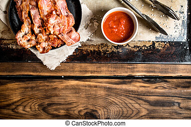 Fried bacon in a frying pan and tomato sauce. On a wooden...