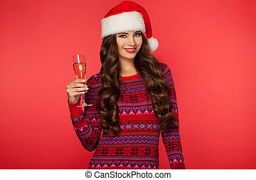 Portrait of a beautiful woman wearing a santa hat smiling, drinking champagne with glasses