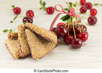 Integral cookies with cherries on a wooden table