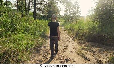 boy walking along the road in the slow motion video - boy...