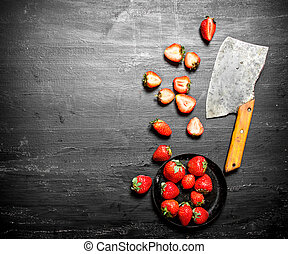 Sliced strawberries with the old hatchet. On the black...