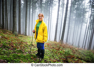 Pretty woman in mistery forest with mist