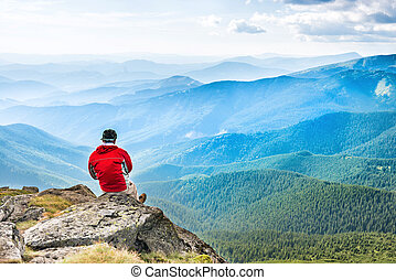 Young man meditates on the top