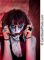 girl makeup zombies posing with crown of thorns near face -...