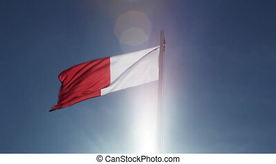 Textile flag of Malta on a flagpole in front of blue sky
