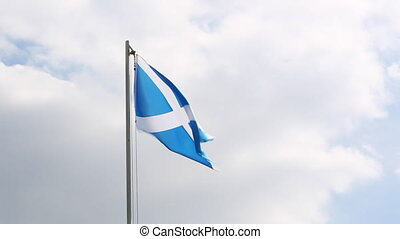 Textile flag of Scotland on a flagpole in front of cloudy...