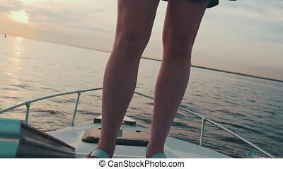 Red hair young girl stand on motor boat Summer evening...
