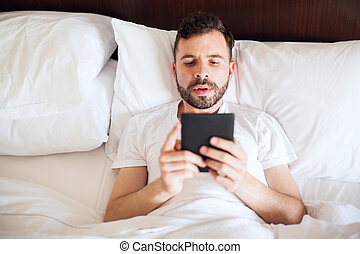 Reading a book in an e-reader - Good looking young man using...
