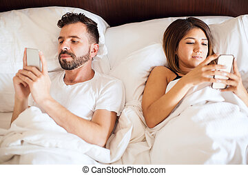 Young couple using their phones in bed - Close look of a...