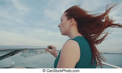 Red hair girl in dress on motor boat Beautiful summer windy...