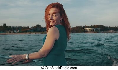 Happy red hair girl in turquoise dress dance on motor boat...