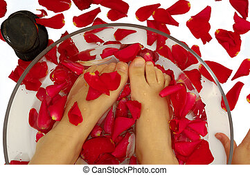 Feet of child in spa with rose petals and stone