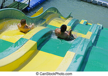 water slip at hte beach - Two people sliding down in the...