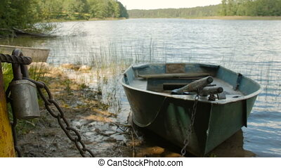 Locked boat by the lake - Boat locked with a chain in the...