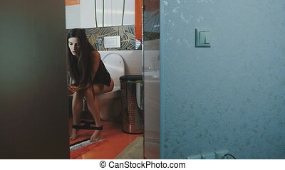 Young girl sitting on toilet without underwear tapping in...