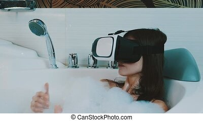 Girl take bath full of foam in bathroom with virtual reality glasses on head