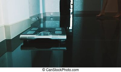 Woman walk on floor stand up on modern scales in apartment....