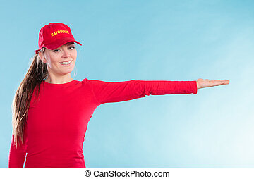 Happy lifeguard woman in cap pointing direction - Portrait...
