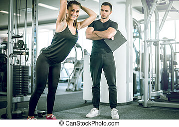 Personal fitness trainer with his client in gym - Young...