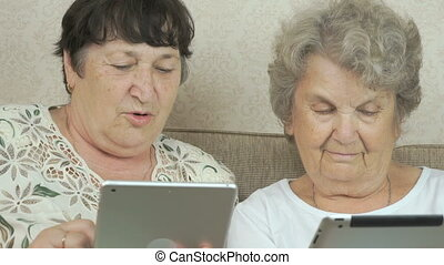 Two elderly grandmothers holding digital tablets - Two...