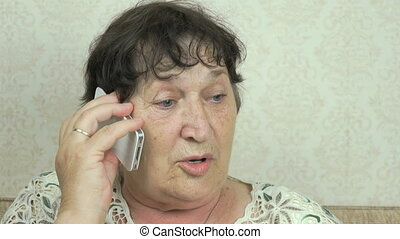 Old woman talks on smartphone to doctor at home - Old woman...