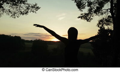 Silhouette of woman in the forest after sunset. Freedom concept.