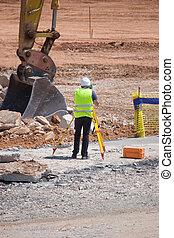 Surveyor taking measurements at a construction site