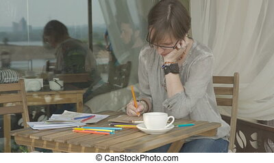Woman is drawing picture sitting outside in cafe or terrace.