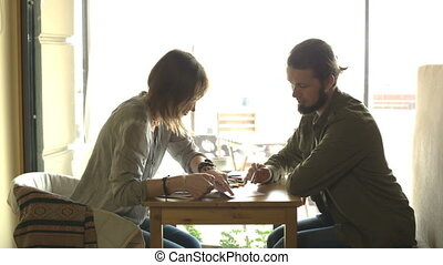 Two people are discussing the sketch or project sitting in cafe .