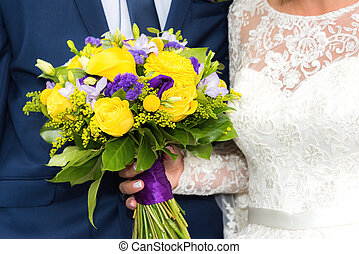 Wedding bouquet of flowers - the groom in a blue suit and a...