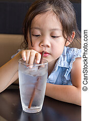 Child Using Straw to Drink Water from Glass