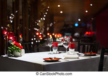 romantic dinner setup, red decoration with candle light in a...